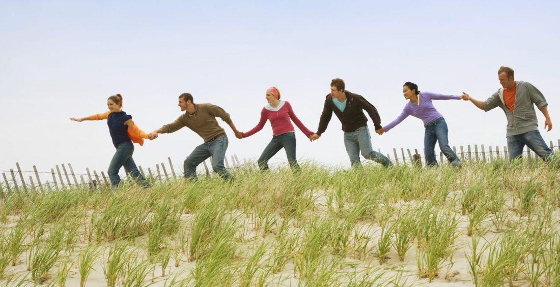 Friends holding hands on beach
